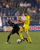 Columbus Crew midfielder Eddie Gaven (12) clears ball away from New England Revolution midfielder Sainey Nyassi (17). The New England Revolution tied Columbus Crew, 2-2, at Gillette Stadium on September 25, 2010.