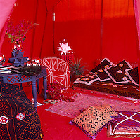 A red rooftop canvas tent furnished with cushions covered in exotic textiles serves as an intimate sitting room or sleeping area