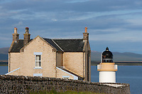 An old fashioned lighthouse constructed with pale salmon-pink bricks seen against the evening sky