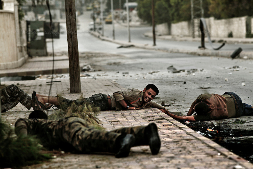 Members of the Al-Baraa Bin Malek Katiba, a part of the Free Syria Army under the Al-Fatah brigade, attempt to rescue a man who was shot by a sniper positioned in a building across the street on a main road that crosses the Bustan Al-Bashar district of Aleppo on October 20, 2012. Several vehicles drove past this man as he looked up in desperation (no one stopped because of the risk of being shot by the sniper). At a moment's notice, the man stood up and began to run towards the members of the Free Syria Army. As he approached the other side of the street, he was shot a second time, falling to the ground. Free Syria Army soldiers crawled through the ground to reach him and pulled them towards a vehicle that rushed him to the hospital. It is not known if he survived. Three civilians were shot on this main road in the space of three hours by the same sniper. ..© Javier Manzano..............