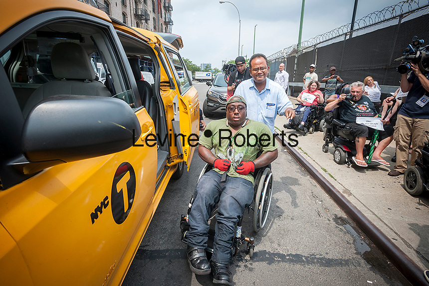 """Dustin Jones arrives via accessible taxi to the Taxis For All Campaign protest in front of Uber headquarters in West Chelsea in New York on Thursday, July 30, 2015. The protesters had a """"roll-in"""" calling on the company to stop discriminating against the disabled by requiring handicapped accessible vehicles. Out of 20,777 Uber cars on the road not one of them is wheelchair accessible. (© Richard B. Levine)"""
