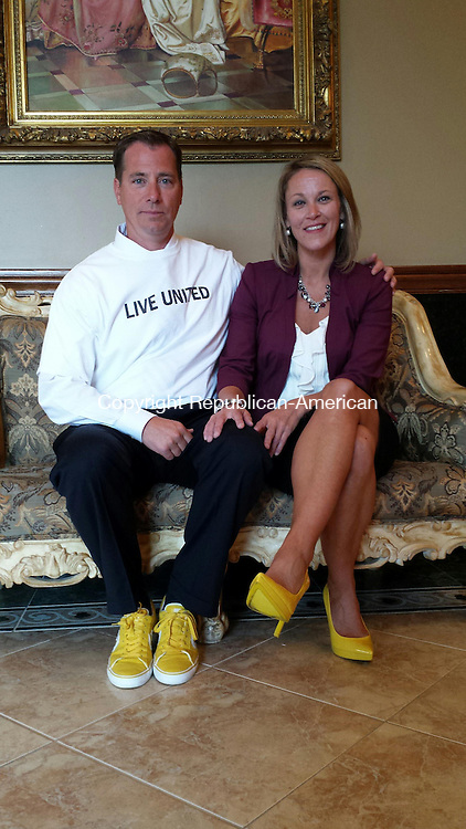 WATERBURY --  Sept. 11, 2014 -- 10_NEW_091114MDP01 -- Walking on sunshine: George A. LaCapra Jr., and his wife Stacy LaCapra, co-chairs of this year's United Way of Greater Waterbury fundraising campaign, show off their yellow shoes that are symbolic of the campaign's title, 'Taking Steps Together.' The two announced the campagn goal of $3.6 million at a gala brakfast at La Bella Vista Wednesday.