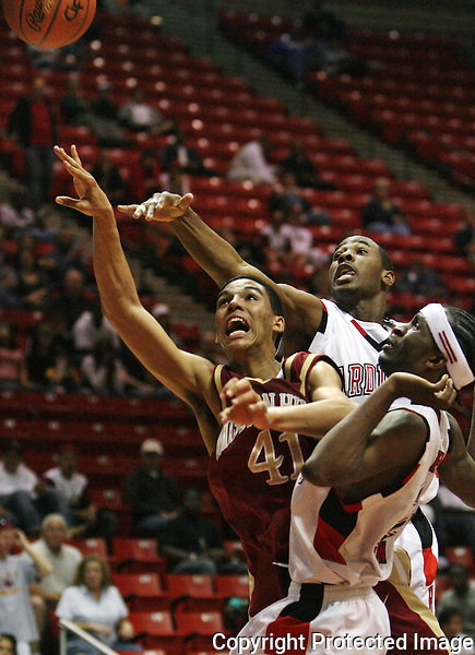 Mission Hills' Michael Traber, center, tries to put up a shot between Hoover's Reggie Lawson, back, and Jevon Carmon during a 2008 playoff game.  photo for North County Times