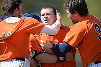 Gettysburg Bullets infielder Mike Elisio (39) is mobbed by teammates including Nate Simon (34 - right)  after the game winning hit during the first game of a doubleheader against the Edgewood Eagles at the Lee County Player Development Complex on March 10, 2014 in Fort Myers, Florida.  Gettysburg defeated Edgewood 3-2.  (Mike Janes/Four Seam Images)