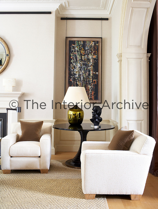 A round glass table displays a marble bust in a corner of this contemporary living room