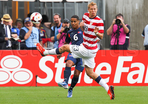 13.07.2013. Sandy, Utah, USA.Cuba defender Joel Colome (6) kicks the ball past the defense of US Men's National midfielder Josh Gatt (23) during the CONCACAF Gold Cup soccer match between USA Men's National team and Cuba at Rio Tinto Stadium in Sandy, UT. USA.