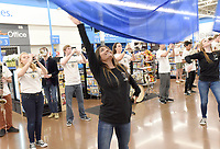 NWA Democrat-Gazette/FLIP PUTTHOFF <br />STRIKE UP THE BAND<br />Madisyn Miranda (cq) (center) performs a flag routine Tuesday April 10 2018 with the Bentonville Pride Marching Band at the Walmart store at the Pleasant Crossing shopping center in Rogers. The high schoool band was on hand to celebrate the national release of the movie, &quot;The Greatest Showman,&quot; said Alisha Pettigrew, a Bentonville band parent. Students performed the song, &quot;This Is Me,&quot; from the movie. Their performance was filmed as part of a marketing promotion for the movie, store personnel said. Students performed from 5 a.m. to 7 a.m. so shopper traffic wouldn't be impeded, Pettigrew said. Band members are used to early hours from traveling to band competitions, she added.