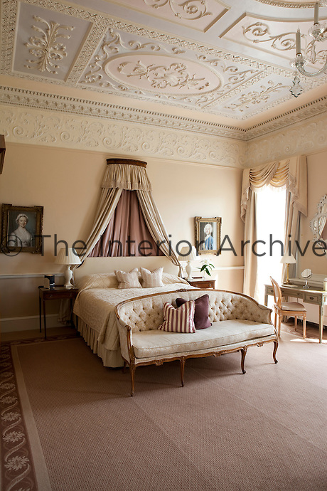 A luxurious bedroom with an ornate plaster work ceiling and double bed with corona.