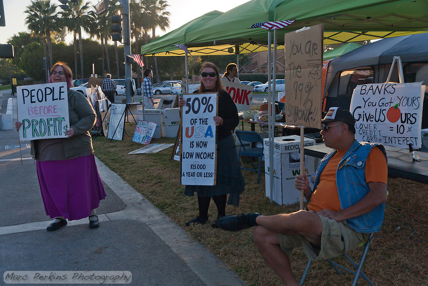 "A number of people gather on a Monday evening at the Occupy Orange County - Irvine camp.  Signs read ""People before Profit$"", ""50% of the USA is now low income $25,000 a year or less"", ""You are the 99% so honk!!"", ""Banks you got yours give us ours!"""