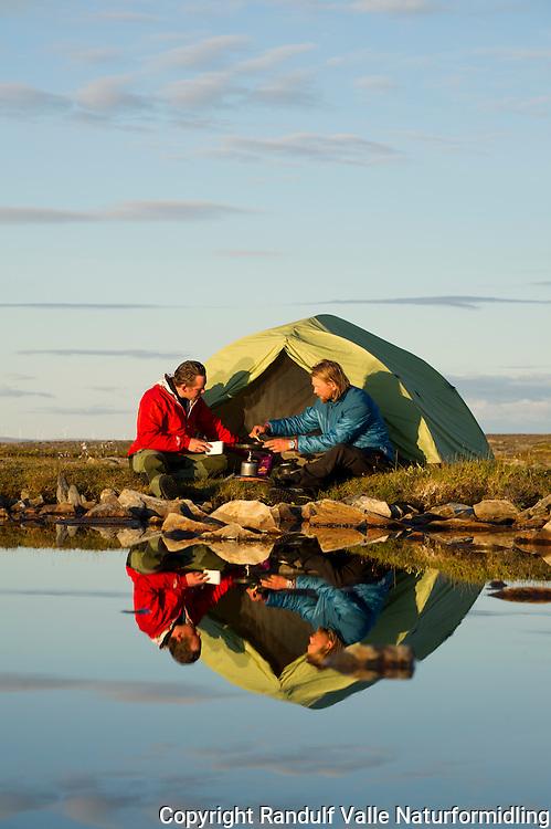 Tom menn lager mat foran teltet om kvelden. ---- Men cooking in front of tent.
