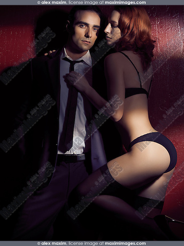 Artistic dramatic photo of a young sexy couple, man wearing a business suit and woman in lingerie holding him by the tie