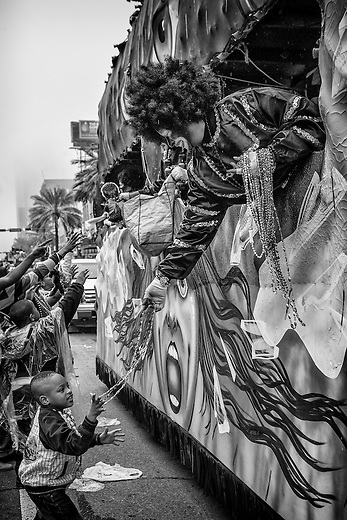 A float rider in the Zulu Social Aid & Pleasure Club's 'Zulu Parade' hands beads to a young parade-watcher on the morning of Mardi Gras on February 12, 2013 in New Orleans, Louisiana.