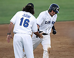 SIOUX FALLS, SD - JULY 9:  Hitting Coach Andy Juday #16 from the Sioux Falls Canaries gives a hand slap to Kevin Dultz #21 after a solo home run in the fifth inning against the Lincoln Saltdogs Tuesday night at the Sioux Falls Stadium. (Photo by Dave Eggen/Inertia)