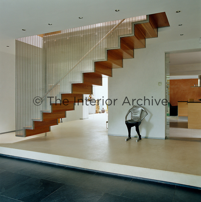 A zig-zag cherrywood staircase enclosed by transparent walls of fine stainless steel mesh seems to float above the limestone floor of the hallway