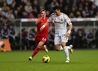 Sunday, 25 November 2012<br /> Pictured: Ki Sung Yueng of Swansea (R) chased by Joe Allen of Liverpool (L).<br /> Re: Barclays Premier League, Swansea City FC v Liverpool at the Liberty Stadium, south Wales.