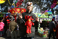 CHINA. A man selling toys during Chinese New Year in Ditan Park in Beijing.  Chinese New Year, or Spring Festival, is the most important festival and holiday in the Chinese calendar In mainland China, many people use this holiday to visit family and friends and also visit local temples to offer prayers to their ancestors. The roots of Chinese New Year lie in combined influences from Buddhism, Taoism, Confucianism, and folk religions.  2008.