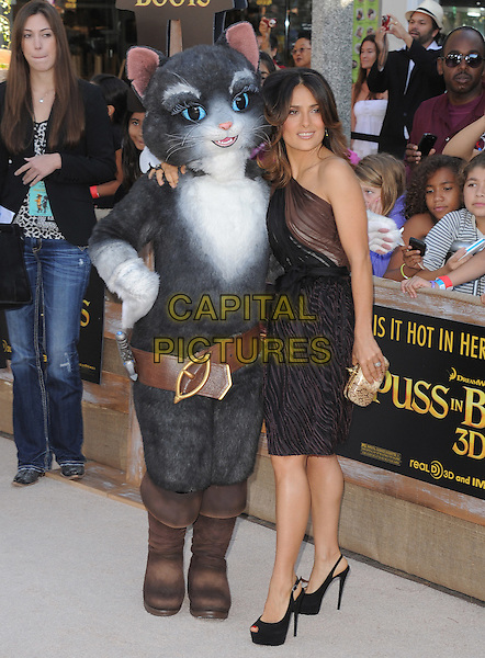 Salma Hayek  .The L.A. Premiere of 'Puss in Boots' held at The Regency Village  Theatre in Westwood, California, USA..October 23rd, 2011 .full length dress black brown sheer one shoulder gold clutch bag costume.CAP/RKE/DVS.©DVS/RockinExposures/Capital Pictures.