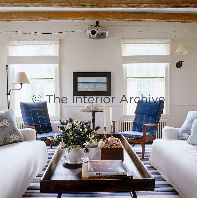 The two windows dictate the symmetry in this simple living room with the matching armchairs and the linen-covered sofas following suit
