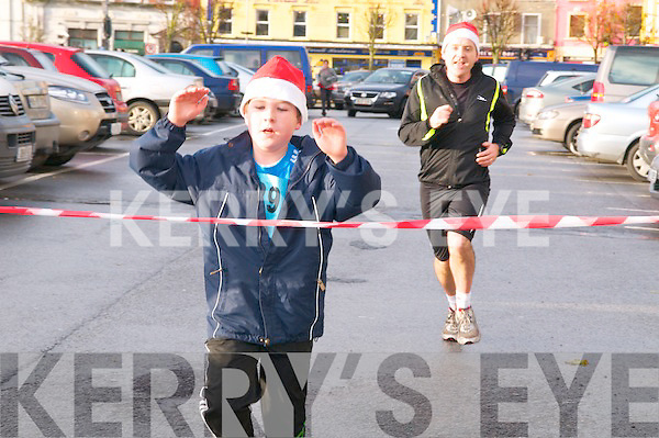 Jingle Bell Run : Father & son Maurice & Eddie Kelly, Listowel crossing the finish line in the 5k run during the Kerry Drusaders Jingle Bell run in Listowel on Sunday last.