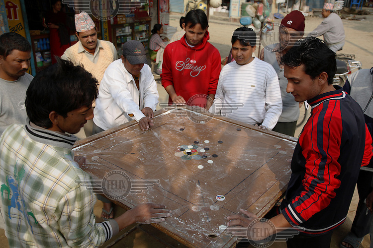 A group of young men playing carrom.