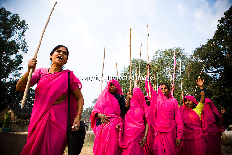 The 47-year-old leader of the Pink Gang, Sampat Pal Devi (left) is a fiesty woman. The barely educated, impoverished mother of five, Sampat Pal Devi has emerged as a messianic figure in the region. Sampath Devi began to work as a government health worker, but she quit soon after because her job was not satisfying enough. She always wanted to work for the poor and not for herself. Taking up issues while being a government worker was difficult, so she decided to quit the job and work for the rights of people...Amidst the gloom of extreme poverty, it's the colour of pink that's calling the shots in this dusty region of Bundelkhand, one of the poorest parts of one of India's northern and most populous states, Uttar Pradesh in India. A gang of vigilantes, called the Gulabi Gang (pink gang) - its 10,000 strong women members wear only pink sarees - is taking up lathi (traditional Indian cudgel) against domestic violence and corruption.