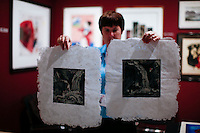 New York City, NY. 06 November 2014. A woman shows an artwork during the IFPDA Print Fair, at the Park Avenue Armory in new york