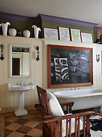 The large panelled bathroom displays a collection of artwork and ceramics