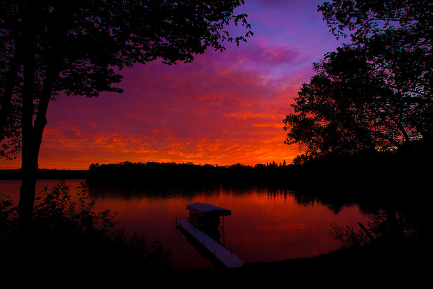 The day's first light reflects off clouds and the water's surface at Serpent Lake near Deerwood, Minnesota.