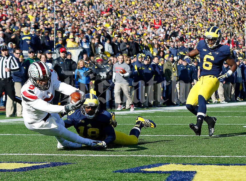 Ohio State Buckeyes quarterback Braxton Miller (5) falls into the end zone for a touchdown as he is tripped up by Michigan Wolverines defensive back Blake Countess (18) in the first quarter of the college football game between the Ohio State Buckeyes and the Michigan Wolverines at Michigan Stadium in Ann Arbor, Michigan, Saturday afternoon, November 30, 2013. The Ohio State Buckeyes defeated the Michigan Wolverines 42 - 41. (The Columbus Dispatch / Eamon Queeney)