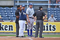 Asheville Tourists manager Fred Ocasio #28 discusses the ground rules with Lexington Legends manager Brian Buchanan #44 and umpires Brad Polk and Randy Rosenberg before a game against the Lexington Legends at McCormick Field on May 14, 2014 in Asheville, North Carolina. The Legends defeated the Tourists 11-2. (Tony Farlow/Four Seam Images)