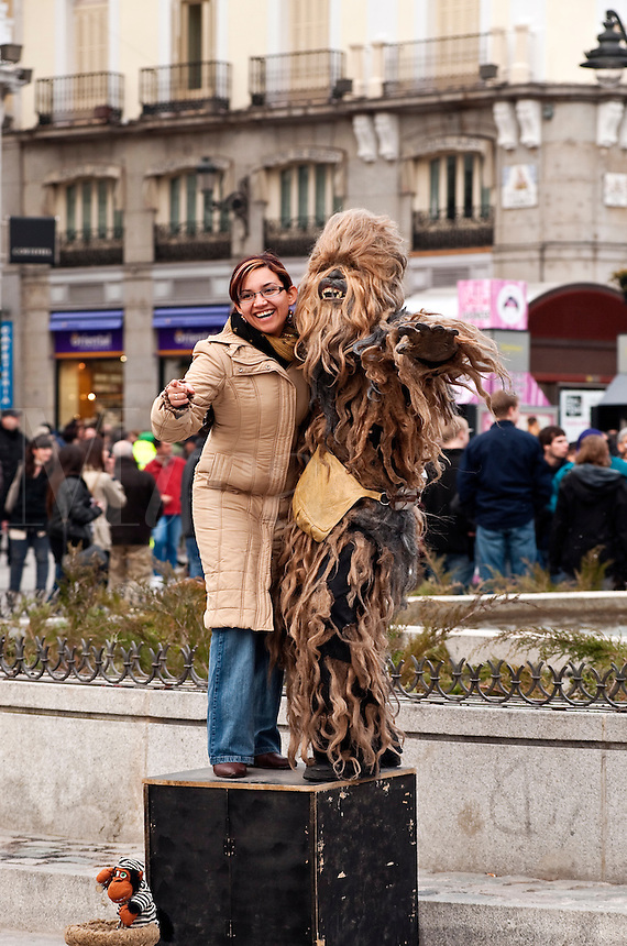 Street performer creature poses with a tourist, Puerta del Sol, Madrid, Spain