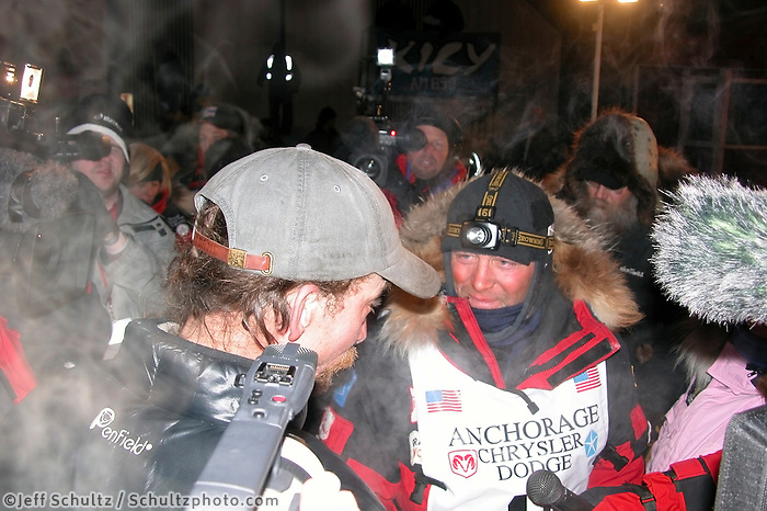 Lance Mackey talks with Paul Gebhardt at the finish line in Nome. Photo by Jon Little.
