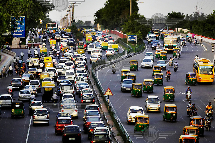 Cars compete with motorised auto-rickshaws, buses and trucks for space on a busy road.