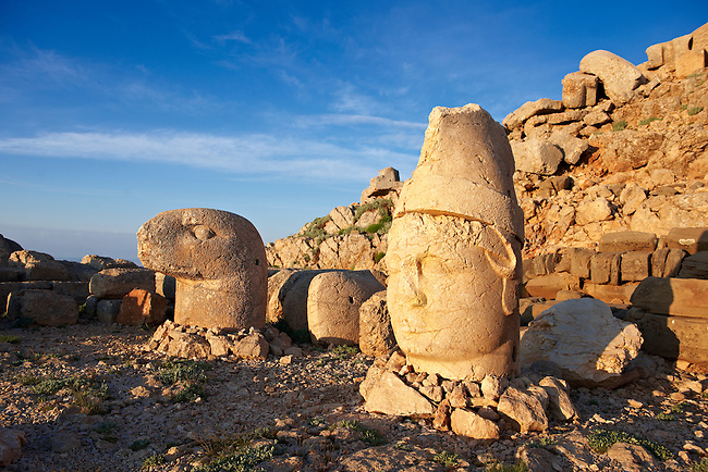 Pictures of the statues of around the tomb of Commagene King Antochus 1 on the top of Mount Nemrut, Turkey. Stock photos & Photo art prints. In 62 BC, King Antiochus I Theos of Commagene built on the mountain top a tomb-sanctuary flanked by huge statues (8–9 m/26–30 ft high) of himself, two lions, two eagles and various Greek, Armenian, and Iranian gods. The photos show the broken statues on the  2,134 m (7,001 ft)  mountain.