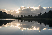 Dawn reflections of clouds and sunrays in Lake Matheson, Westland Tai Poutini National Park, West Coast, UNESCO World Heritage Area, South Westland, New Zealand, NZ