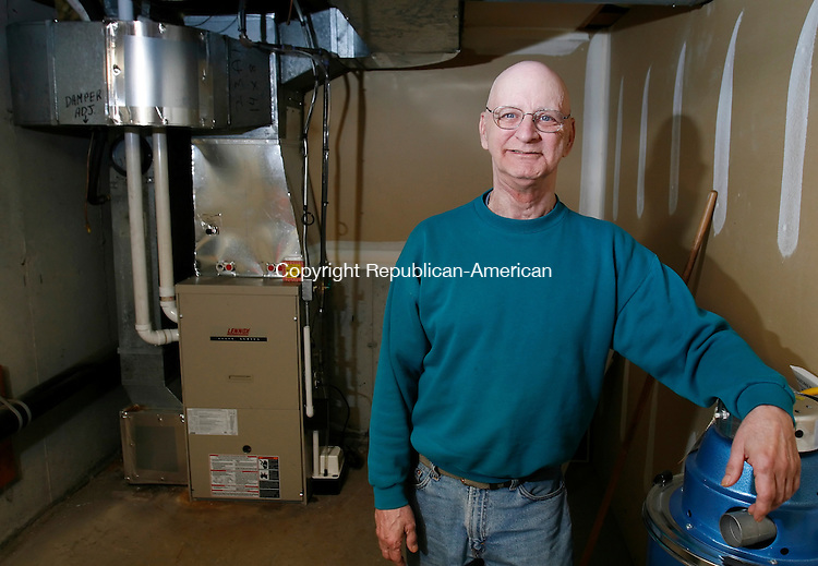 WATERBURY, CT, 12/27/08- 122708BZ01- Charles Lestage poses near his new furnace in the basement of his Waterbury home.  Lestage, who is on a fixed disability income and did not have enough money to replace his old furnace, received more then $4,000 in donations after his story appeared in the Republican-American.<br />  Jamison C. Bazinet Republican-American