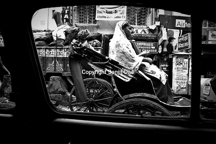 A rickshaw puller is seen taking customers through the busy street in Calcutta, India. 93 out of every 100 rickshaw pullers are homeless. They sleep after the city sleeps and wake up before everyone else does. Many of them are the sole bread earners for their family. Many plus 40. Many minus any other specialisation for any other job. Of the twenty four thousand rickshaw pullers, only 387 have licenses. .Many rickshaw pullers earn a meagre wage of 100-150 rupees (US $ 2.25-3.5) a day of which they have to give a daily rickshaw rent of 60 (US$ 1.35) rupees to the agent at the end of the day.