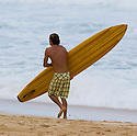 Aamion Goodwin carrying a wooden Board after a surf on the North Shore in Hawaii