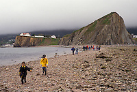 Gaspe Peninsula, Perce, Quebec, Canada, Rocher Perce, Gulf of St. Lawrence, People walking to and from Rocher Perce (Perce Rock) at low tide on the Gulf of St. Lawrence in Perce on Gaspe Peninsula in Quebec.