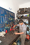 HURGHADA - EGYPT - 03 March 2015 -- Taha leaning to repair motorcycle part in mechanical workshop. -- Photo: Kimmo HAGMAN / EUP-IMAGES
