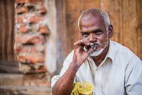 Portrait of a man smoking a cigar on the streets of Negombo on the West Coast of Sri Lanka, Asia. This is a portrait of a man smoking a cigar on the streets of Negombo on the West Coast of Sri Lanka, Asia.