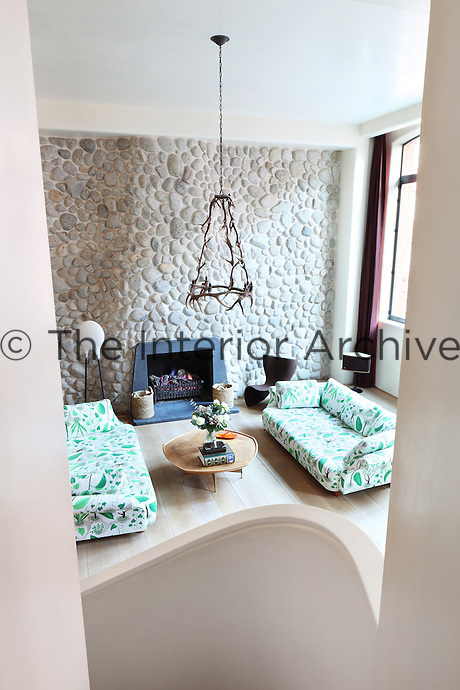 View of the open plan living area from the curved staircase leading to the gallery