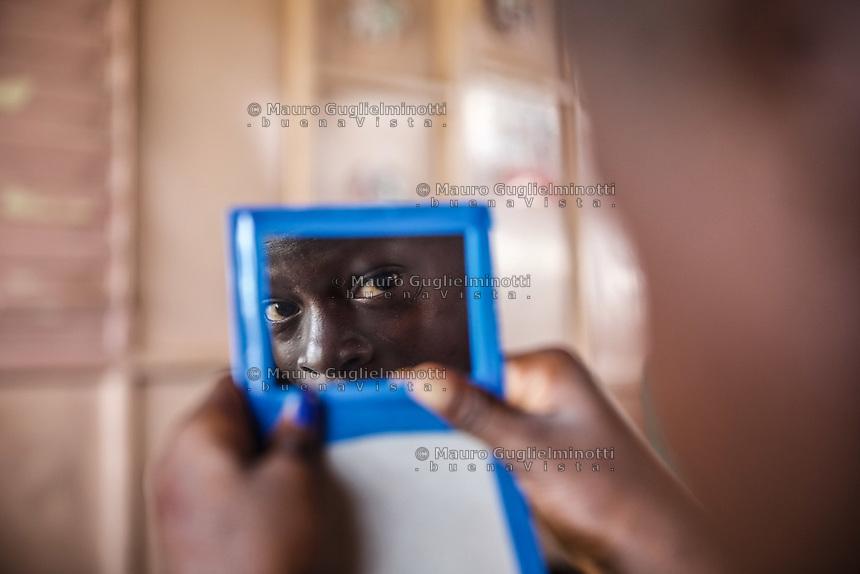 Benin. Cotonou . foyer salesiano Don Bosco Ritratto di bambino di colore, occhi riflessi in uno specchio