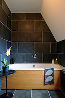 Brazilian black slate flooring is used for the walls and floors in a modern bathroom where the bath has a wooden front panel.