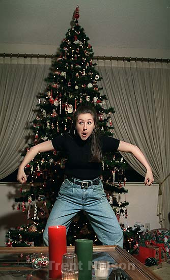 Christina Nelson posing in front of christmas tree at Christmas party<br />