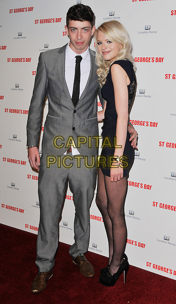 guest & Hetti Bywater.The 'St George's Day' world film premiere, Odeon Covent Garden cinema, Shaftesbury Avenue, London, England..August 29th, 2012.full length grey gray suit white shirt black tie dress blue sleeveless side .CAP/WIZ.© Wizard/Capital Pictures.