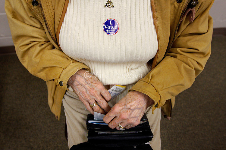 A woman puts away her ID after voting in a polling station while U.S. Presidential hopeful Mike Huckabee (R-AR) meets with potential supporters in Columbia, South Carolina, on Saturday, January 19, 2008. (Photo by: Yana Paskova for The New York Times)..Assignment ID: 30055282G..........