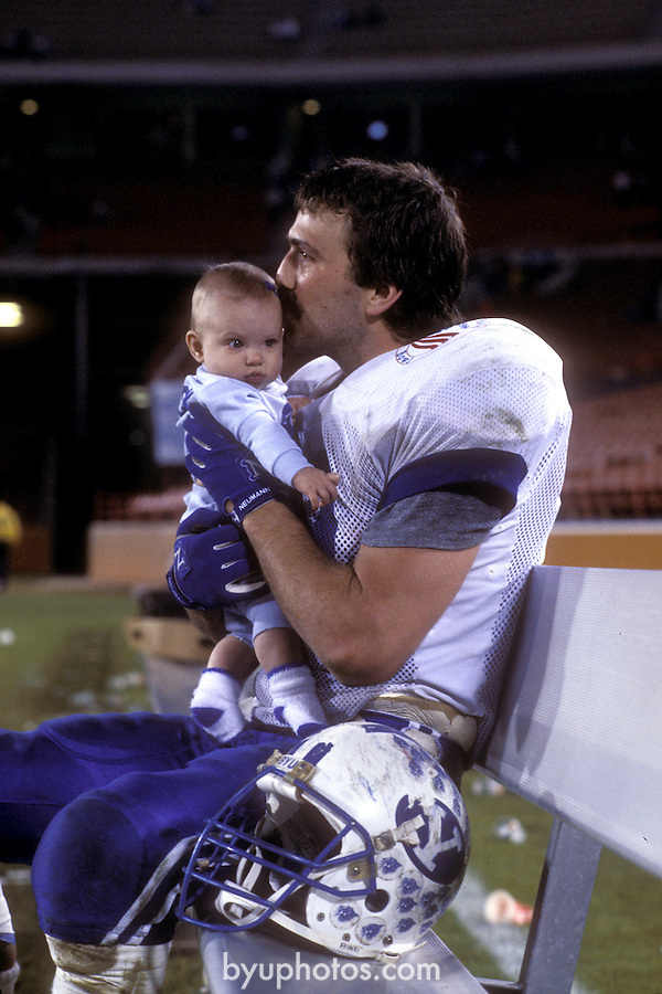 FTB 1986 Freedom Bowl-Buck <br /> <br /> BYU FTB Football vs UCLA University of California Los Angeles at the Freedom Bowl.<br /> 99 Jason Buck holding baby<br /> <br /> Dec. 30, 1986<br /> <br /> Photo by Mark A. Philbrick/BYU<br /> <br /> &copy; BYU Photo 2012<br /> All Rights Reserved<br /> photo@byu.edu (801) 422-7322
