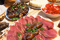 Montenegrin food speciality: Smoked and dry cured ham and smoked sausages on a plate.. Plates with tomatoes and cheese. Durovic Jovo Winery, Dupilo village, wine region south of Podgorica. Vukovici Durovic Jovo Winery near Dupilo. Montenegro, Balkan, Europe.