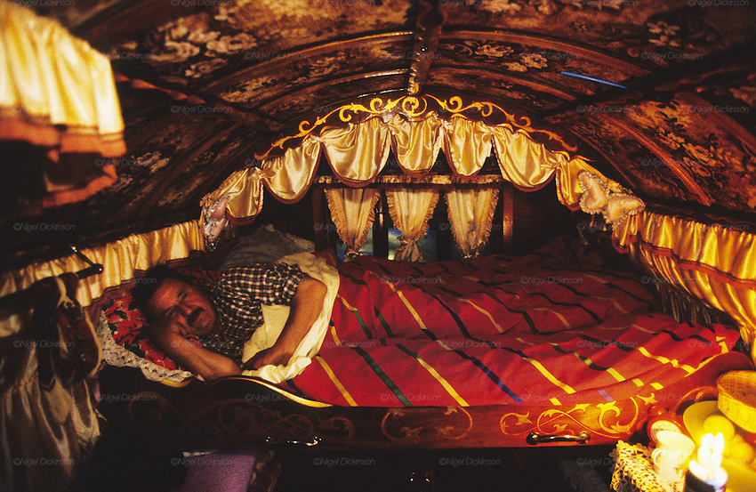 Leslie curls up to sleep in his traditional English bow topped Gypsy wagon. Midlands, England 2000